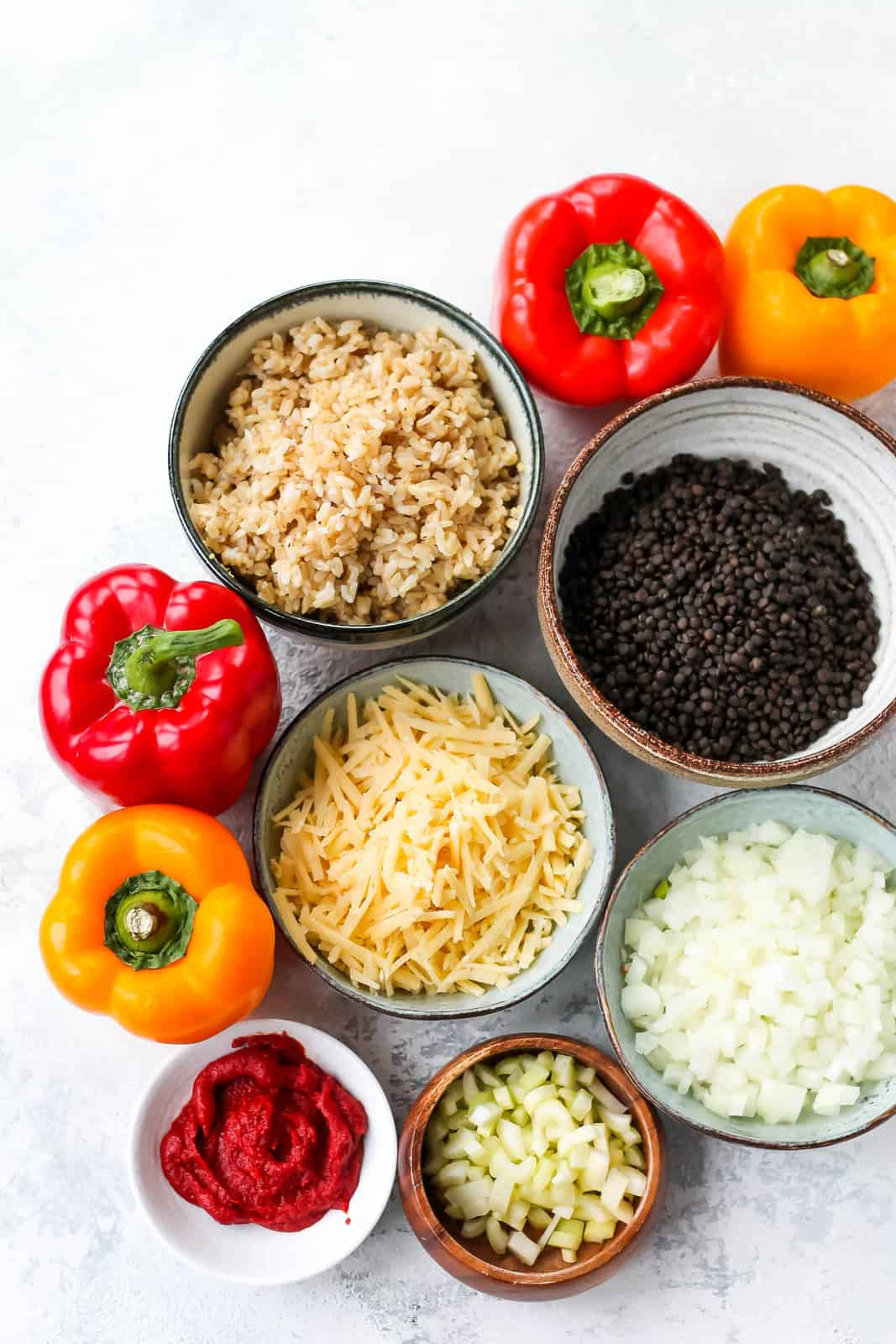 red and yellow peppers, brown rice, black lentils, grated cheese, tomato paste, diced onion, and diced celery on a grey background
