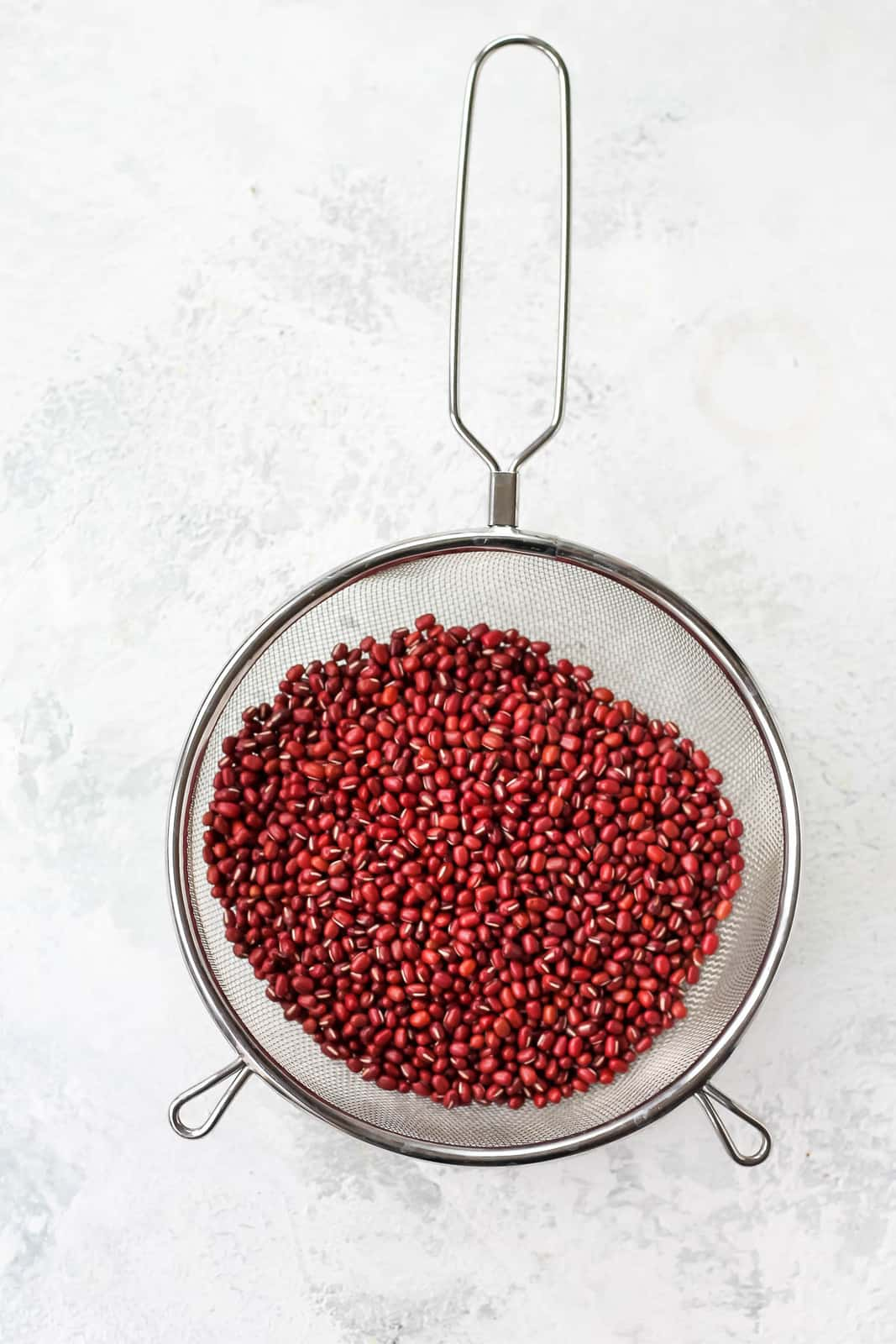 overhead photo of adzuki beans in a mesh strainer on a grey background