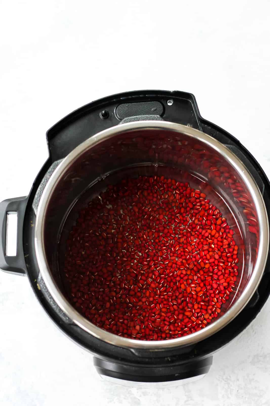 overhead photo of adzuki beans and water in an instant pot