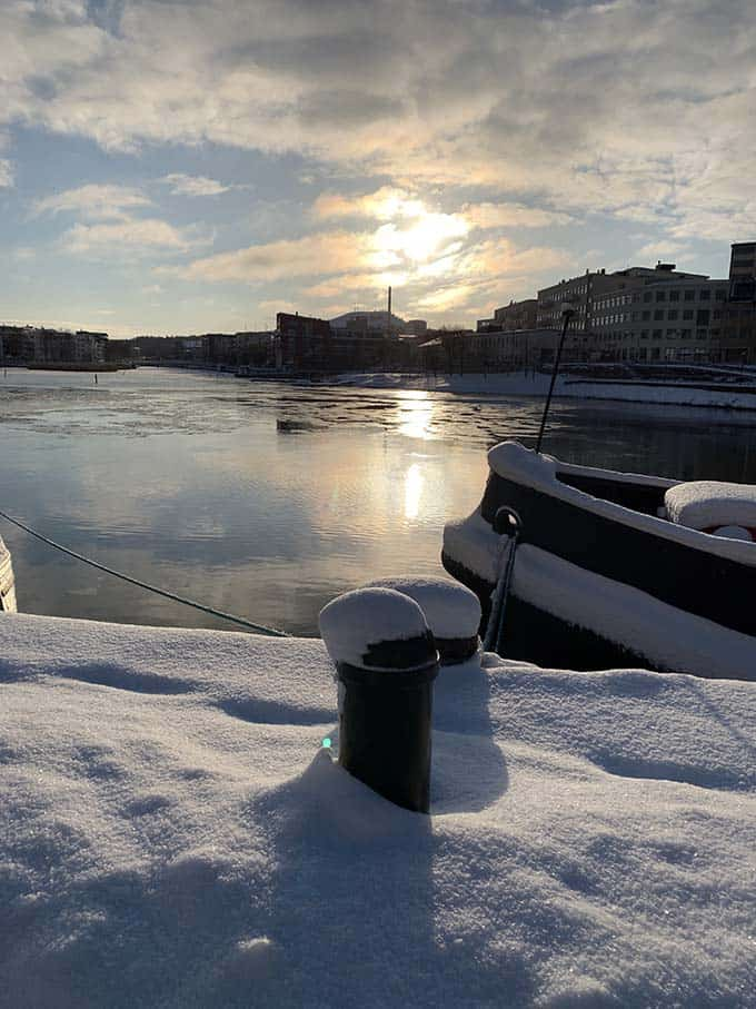 sunlight reflecting on water and snow on a boardwalk and boats in stockholm