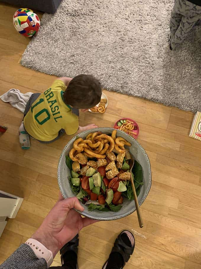 a woman's hand holding a bowl of salad topped with french fries