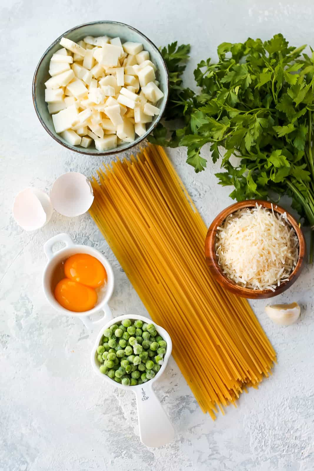 spaghetti, egg yolks, diced halloumi, frozen peas, parmesan cheese, and parsley on a grey background