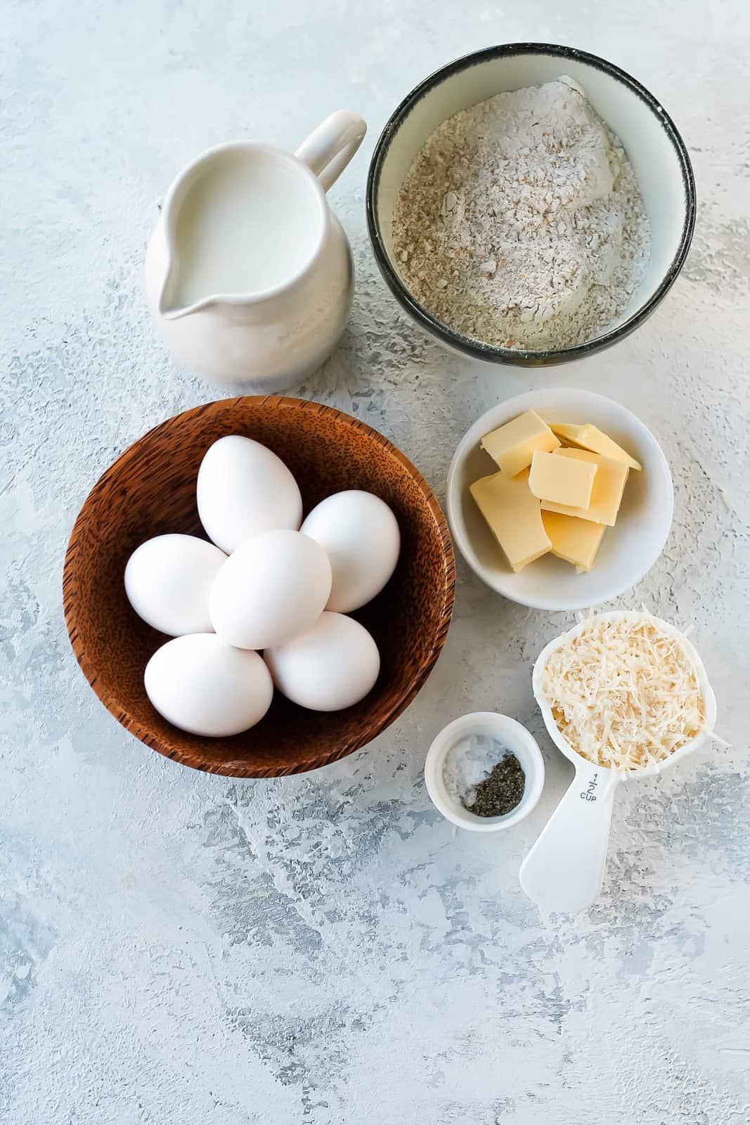 eggs, milk, flour, butter, parmesan, salt, and pepper on a grey background