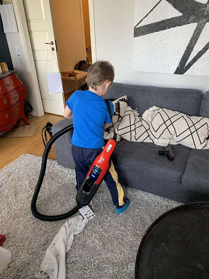 a boy vacuuming a sofa with a red vacuum