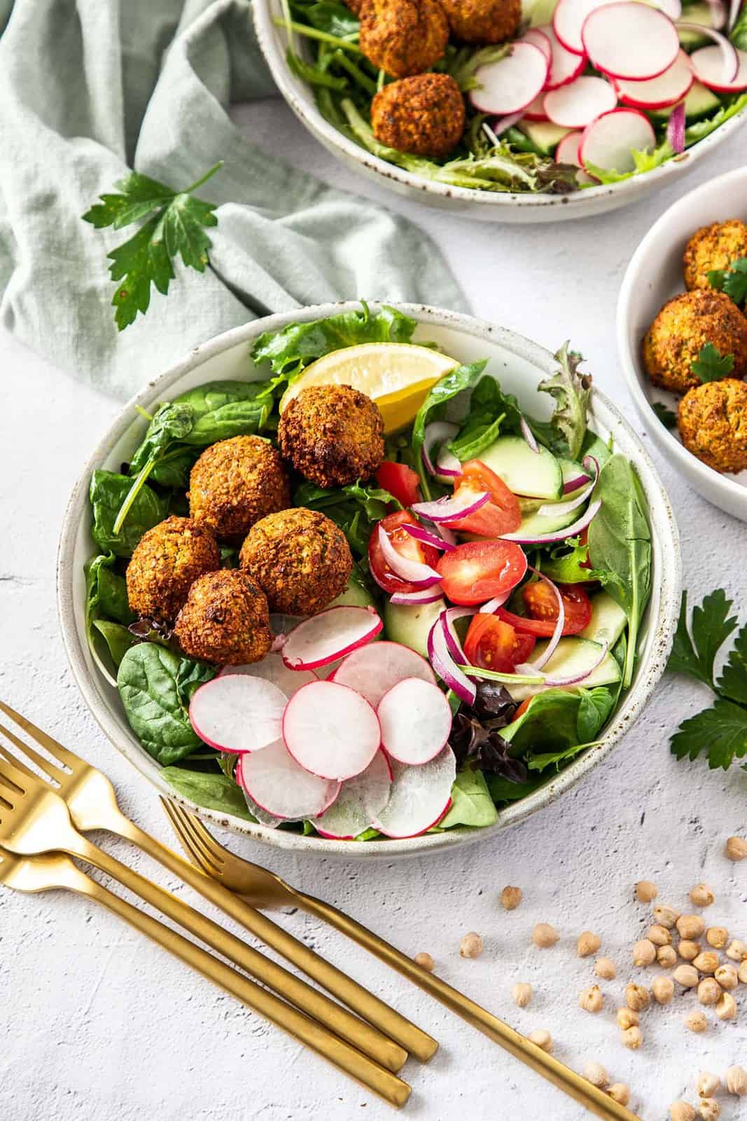 overhead photo of falafels on top of a blue bowl of salad