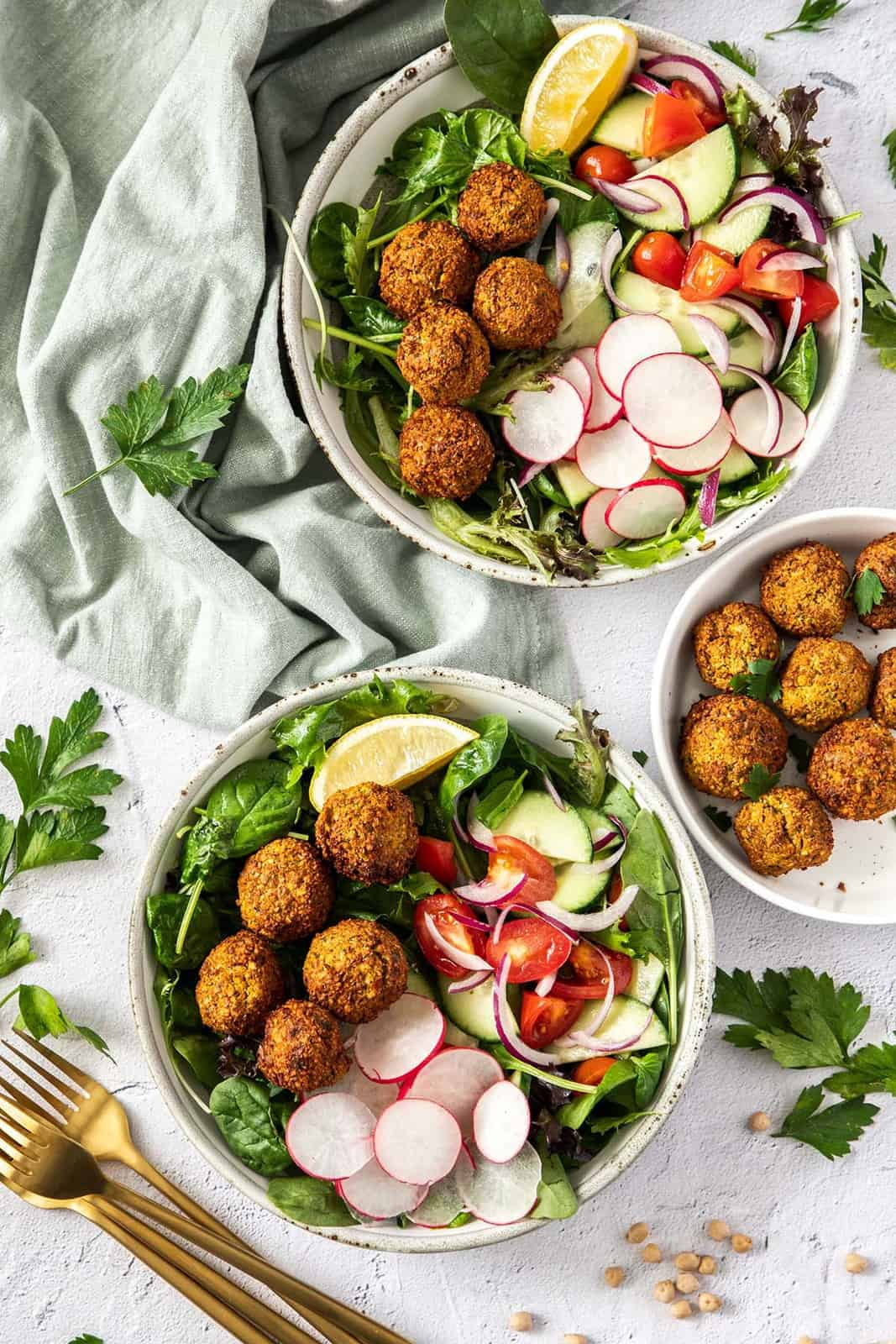 overhead photo of two bowls of salad topped with air fryer falafels