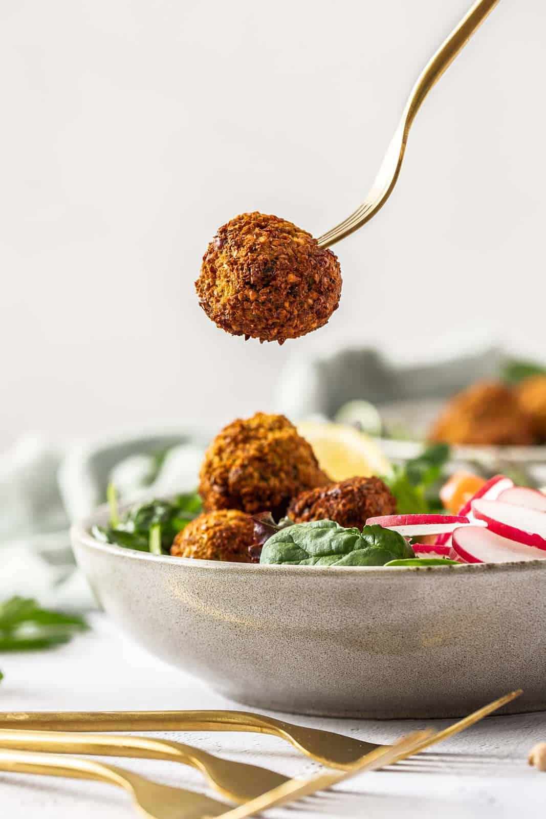 a falafel ball on a gold fork being held over a bowl of salad