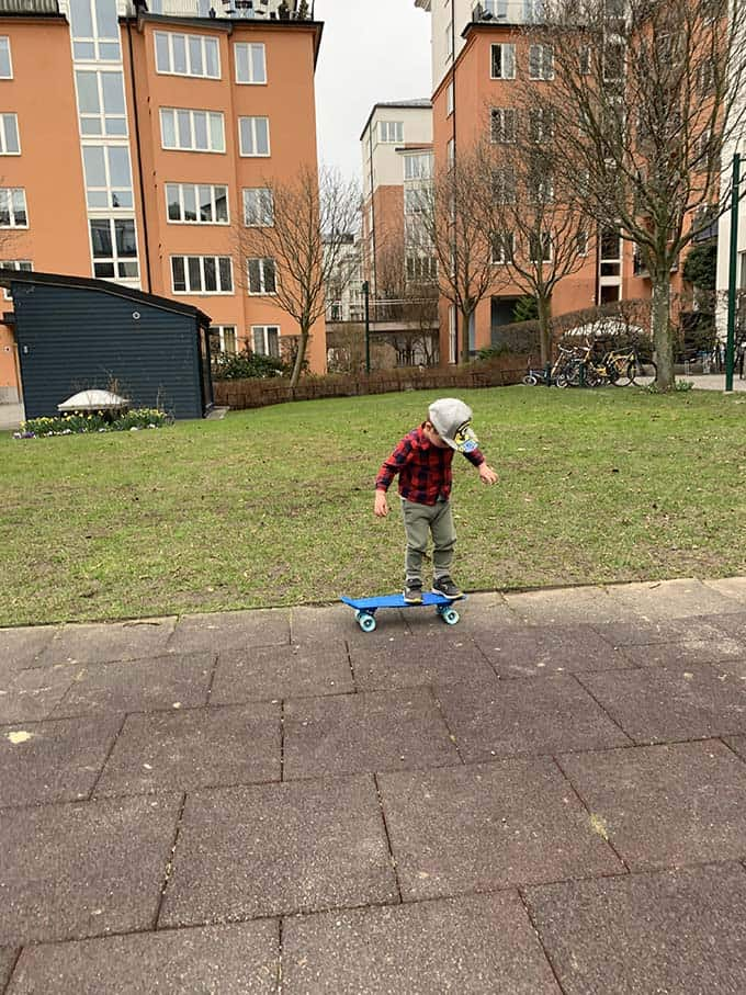 a little boy in a plaid shirt standing on a blue skateboard