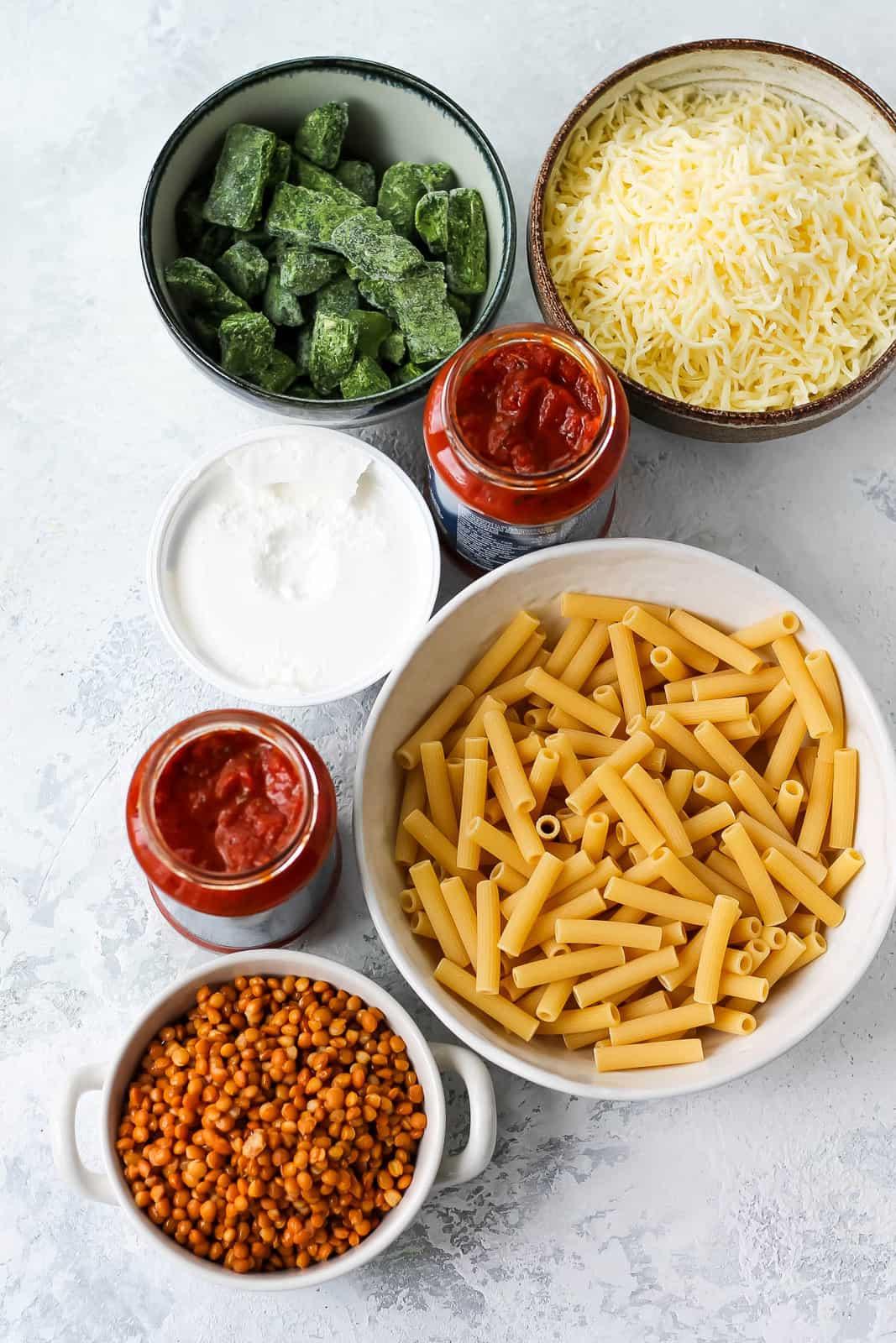 pasta, frozen spinach, mozzarella, ricotta, marinara sauce, and lentils on a grey background