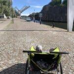 a green bike wagon with two boys watching a bridge open