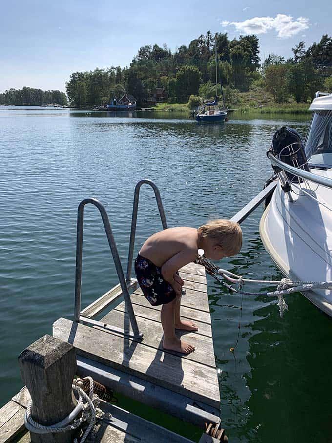 a boy standing on a dock beside a boat