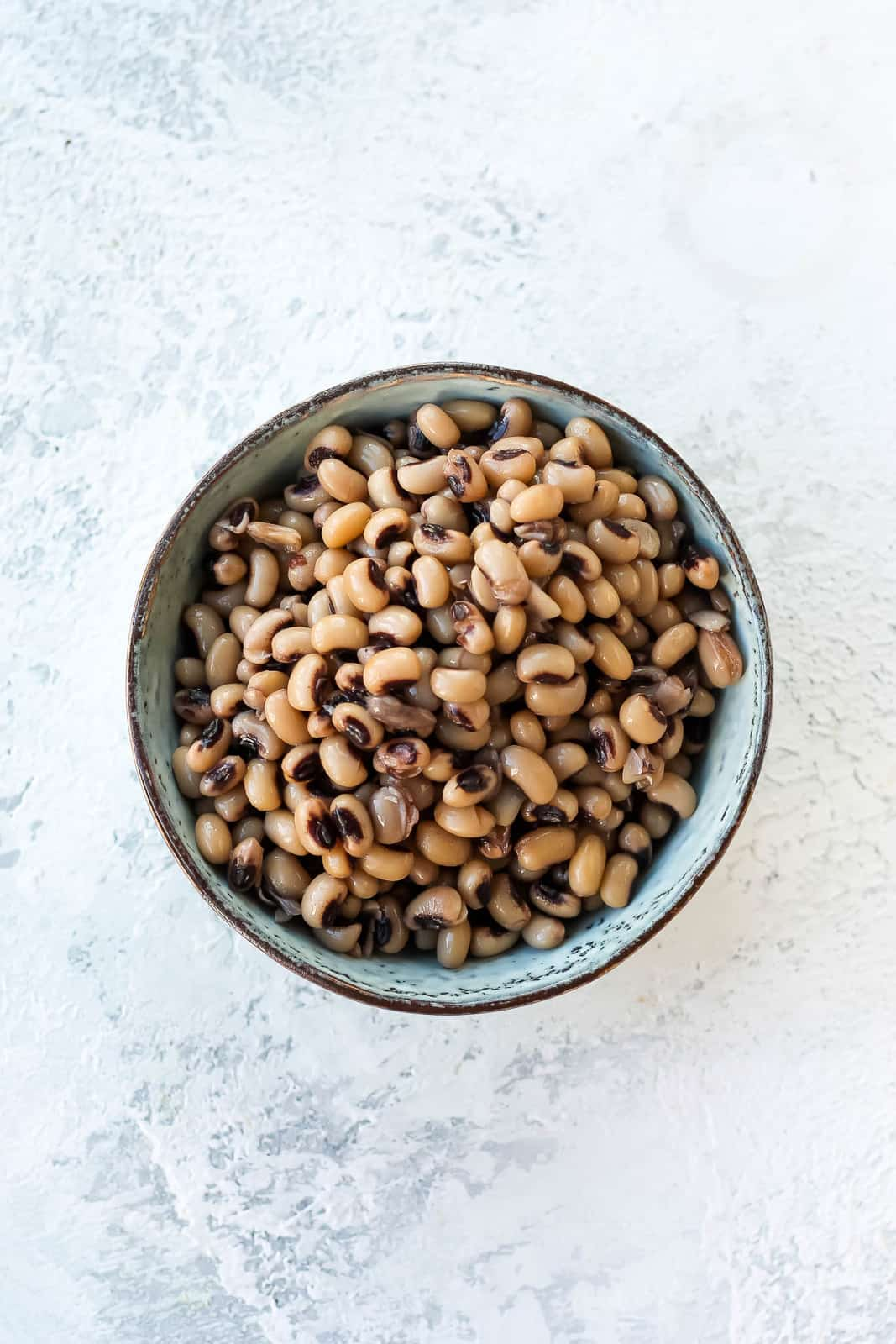 overhead photo of cooked black eyed peas in a blue bowl