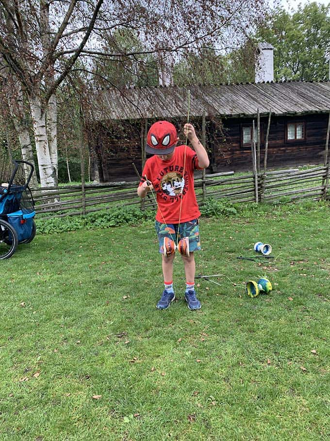 a boy in a red shirt learning to use a yoyo on the grass