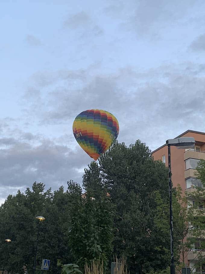 a rainbow hot air balloon floating over an apartment buildig