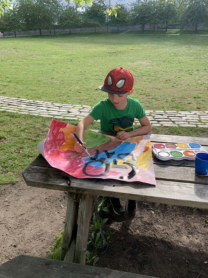 a boy in a green t-shirt painting a sign at an outdoor picnic table