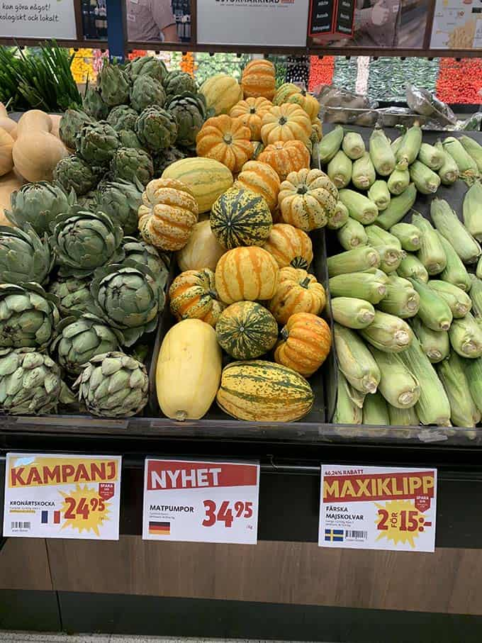 a display of squash, corn, and artichokes in a grocery store