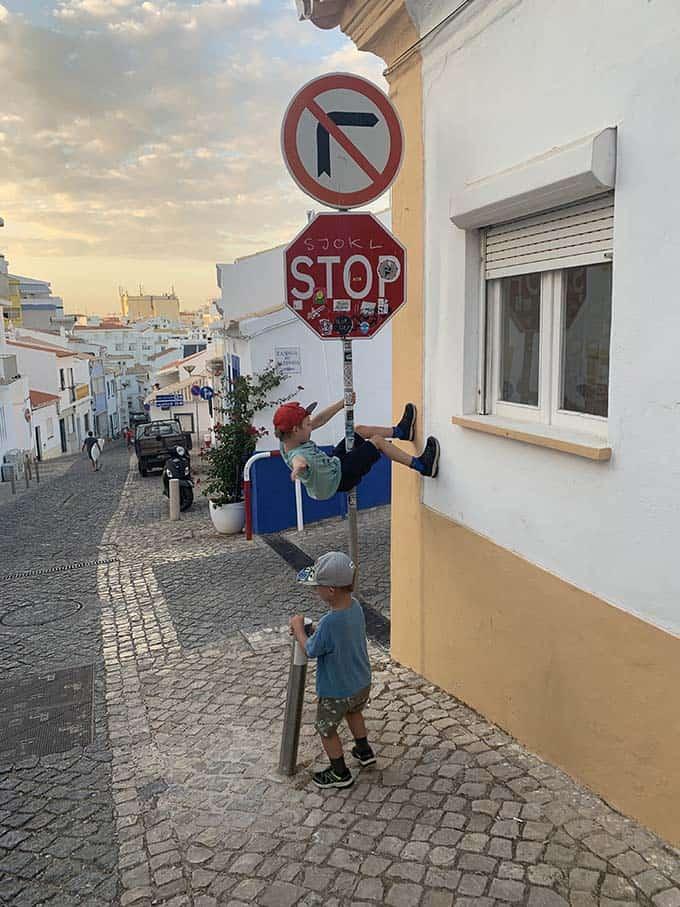 two boys climbing a stop sign
