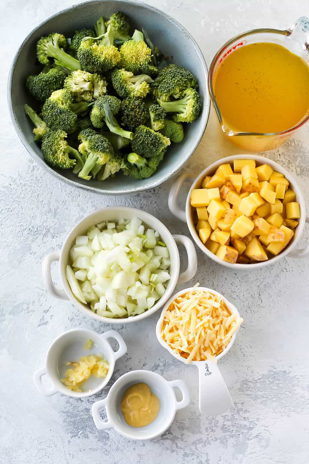 broccoli, vegetable broth, potatoes, onion, garlic, cheddar, dijon mustard, and oil on a grey background