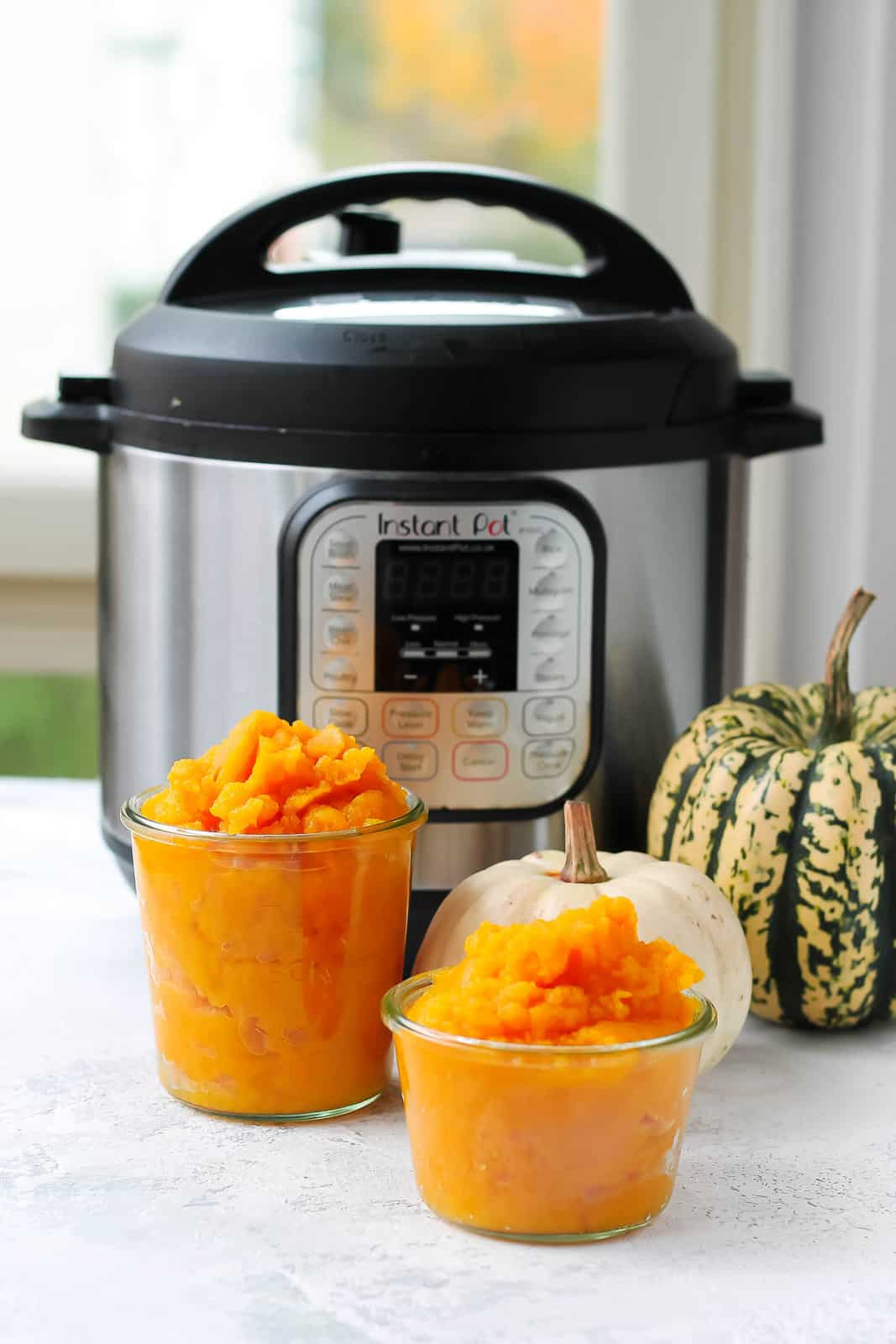 two jars of homemade pumpkin puree in front of an instant pot