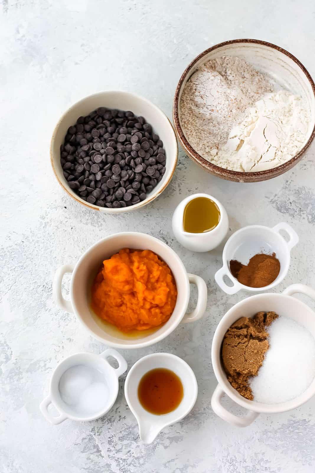 pumpkin purée, chocolate chips, flour, spices, sugar, vanilla, and salt on a grey background